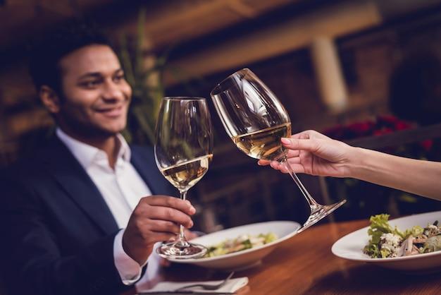 Homem e uma mulher estão bebendo vinho em um encontro em um restaurante.