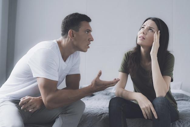 Homem e uma mulher estão sentados na beira da cama e xingando