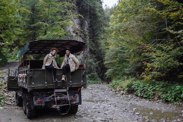 Homem e uma mulher que estão sentados em um caminhão aberto em um fundo de árvores e montanhas. retrato de viajantes