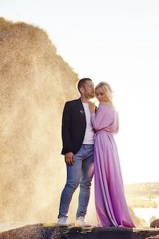 Homem e uma mulher se abraçando no verão ao pôr do sol em lindas roupas. casal apaixonado fica na costa nas rochas ao sol, se abraçando e beijando nos salpicos de água. vestido rosa