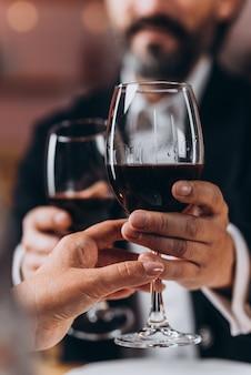 Homem e uma mulher segurando juntos um copo de vinho tinto em close-up.