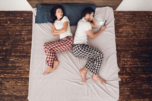 Homem, é, usando, cellphone, e, mulher, encontrar-se cama