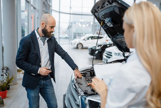 Homem e vendedora escolhendo automóveis na concessionária. cliente e vendedor em showroom de veículos, homem comprando transporte, negociante de automóveis