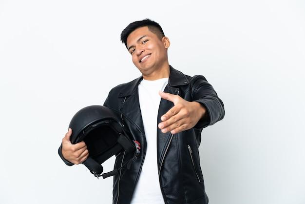 Homem ecudoriano com capacete de motociclista isolado na parede branca apertando as mãos para fechar um bom negócio