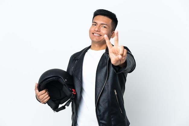 Homem ecudoriano com capacete de motociclista isolado no branco, sorrindo e mostrando sinal de vitória