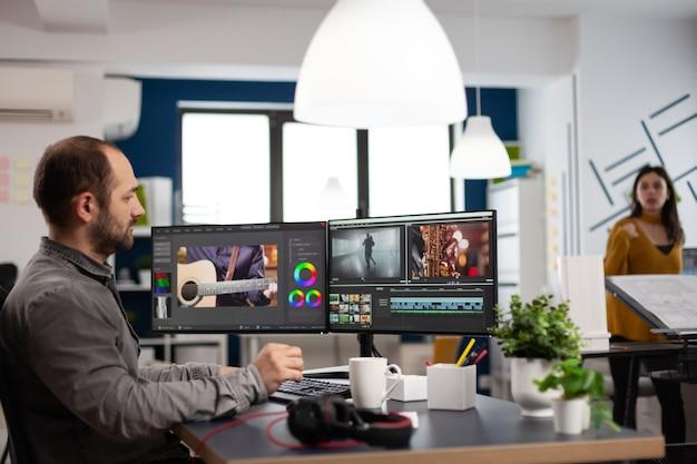 Homem editor de vídeo editando projeto de filme trabalhando em agência de multimídia de criatividade start up