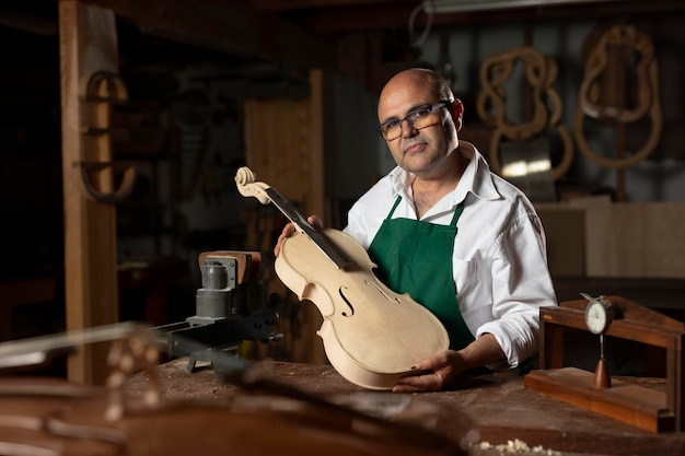 Homem elaborando um instrumento em sua oficina