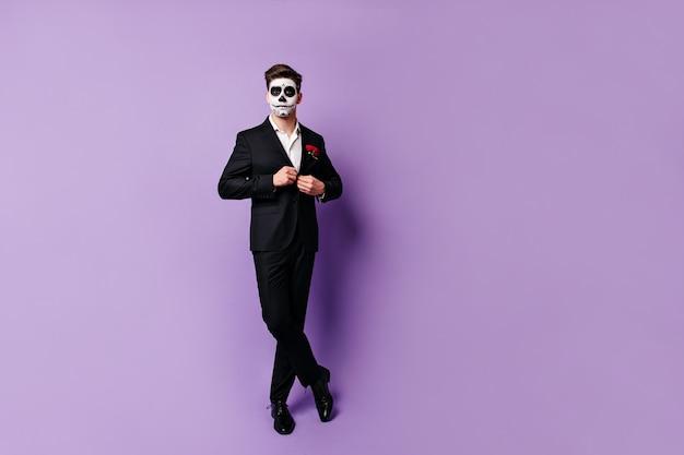 Homem elegante abotoando a jaqueta clássica preta e posando em um estúdio relaxado na máscara para o baile de máscaras.