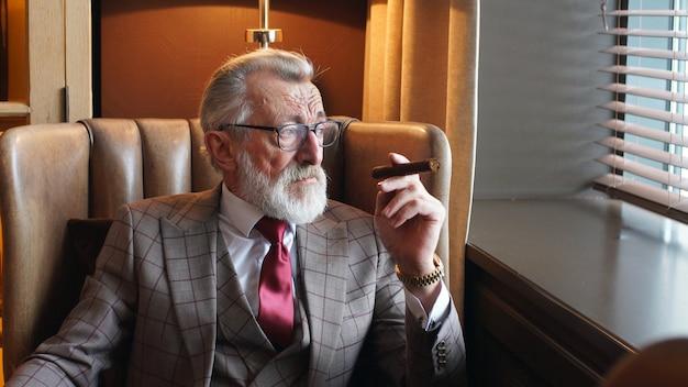 Homem elegante, atencioso e grisalho de terno e óculos está sentado em uma cadeira perto da janela