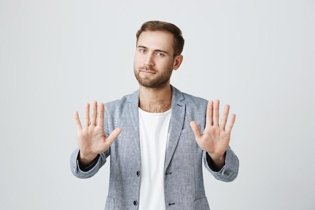 Homem elegante barbudo bonito mostra as palmas das mãos, diga parar