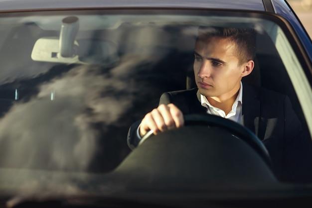 Homem elegante bonito atraente em um terno de negócio dirigindo um carro caro