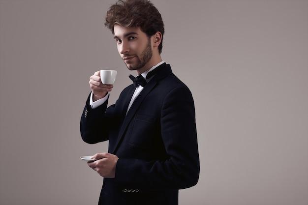 Homem elegante bonito com cabelos cacheados no smoking segurando uma xícara de café expresso
