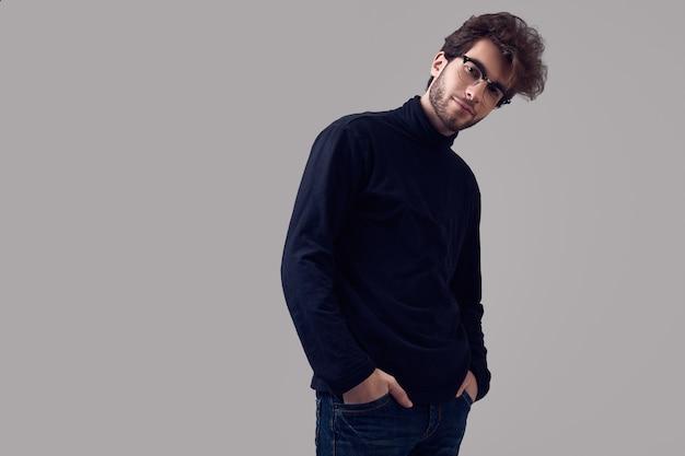Homem elegante bonito com cabelos cacheados, usando óculos e gola alta preta