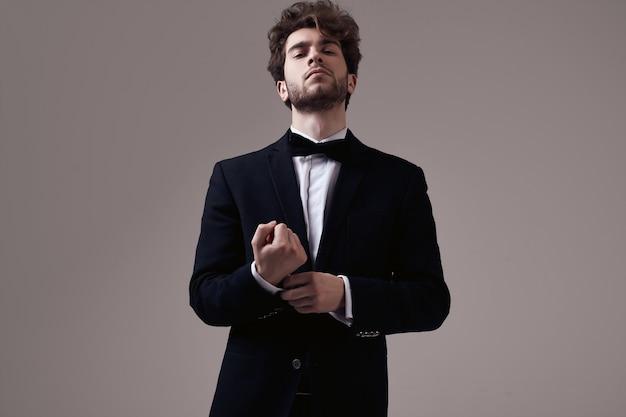 Homem elegante bonito com cabelos cacheados, vestindo smoking