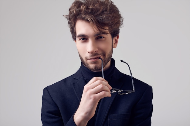 Homem elegante bonito com cabelos cacheados, vestindo terno e óculos
