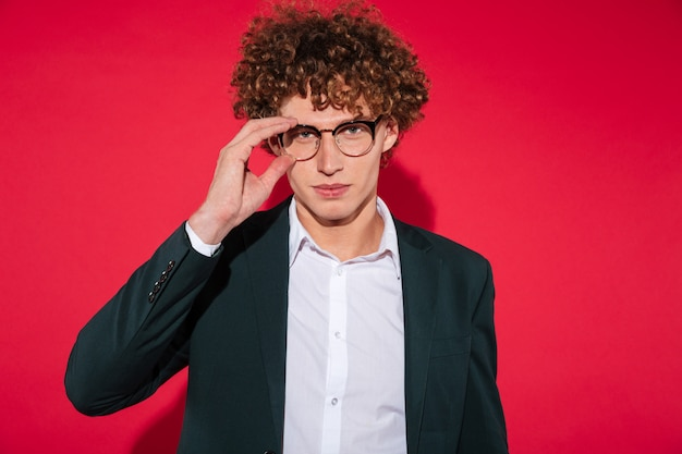 Homem elegante bonito na camisa branca e posando de óculos