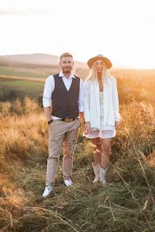 Homem elegante bonito na camisa, colete e calça e mulher bonita boho no vestido, jaqueta e chapéu andando no campo com fardos de palha