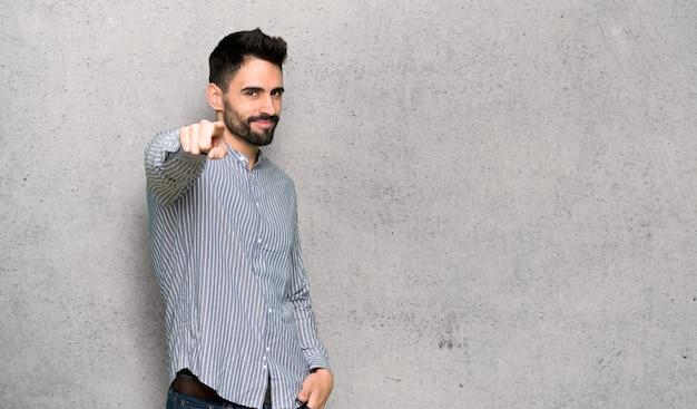 Homem elegante com camisa aponta o dedo para você com uma expressão confiante sobre a parede texturizada