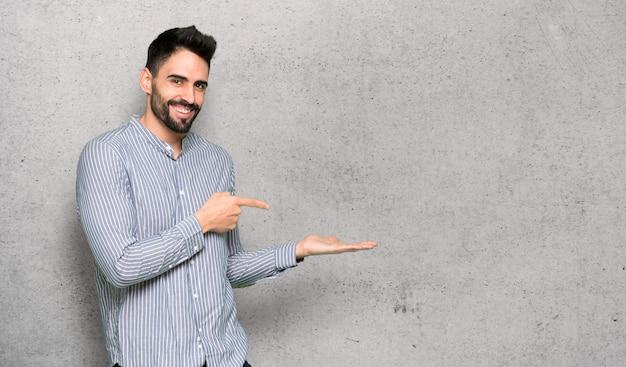 Homem elegante com camisa segurando copyspace imaginário na palma da mão para inserir um anúncio sobre parede texturizada