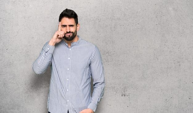 Homem elegante com camisa tendo dúvidas e pensando sobre parede texturizada