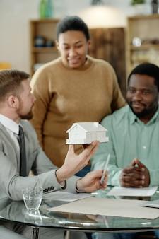Homem elegante com modelo de casa aconselhando casal negro sobre compra de imóveis reunido à mesa
