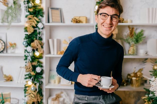Homem elegante com rosto emocional positivo, posando para a câmera com uma xícara de café na acolhedora sala com árvore cristmas.