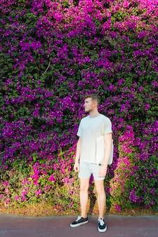 Homem elegante com saco de pano em pé no parque a desviar o olhar