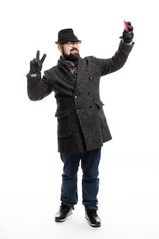 Homem elegante com uma barba, vestida com um casaco elegante e chapéu faz selfie. altura toda. isolado sobre a parede branca. vertical.