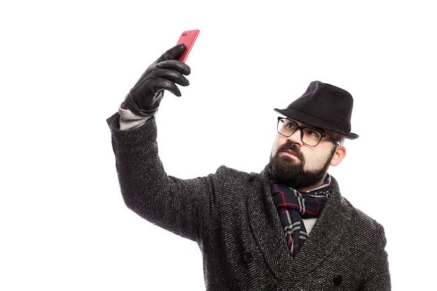 Homem elegante com uma barba, vestida com um casaco elegante e chapéu faz selfie. isolado sobre a parede branca.