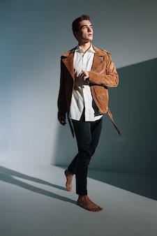 Homem elegante com uma jaqueta marrom sobre um fundo cinza e uma inclinação em forma de sombras na parede.