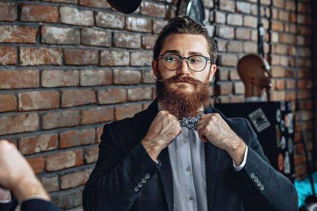 Homem elegante de óculos, barba e bigode, olhando-se no espelho e endireitando uma gravata borboleta no colarinho.