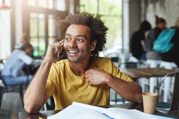 Homem elegante de pele escura com cabelo encaracolado, vestindo uma camiseta amarela cercado de livros, descansando em uma cafeteria aconchegante, bebendo café e falando ao celular
