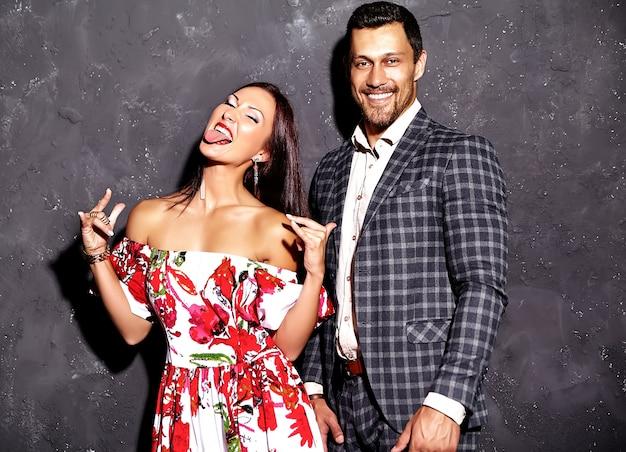 Homem elegante de terno com mulher bonita posando perto de parede cinza
