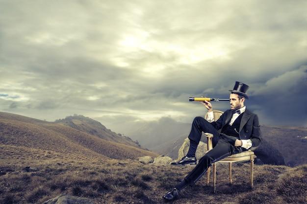 Homem elegante, descobrindo a natureza com escopo.