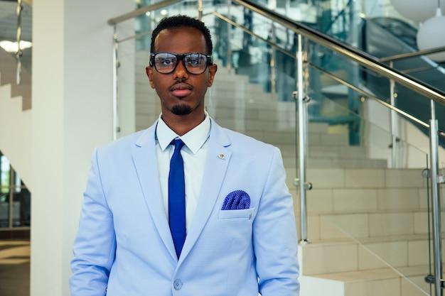 Homem elegante e bem-sucedido empresário africano americano bonito em um elegante terno de luxo posando na rua centro de negócios escritório fundo arranha-céu modelo de moda