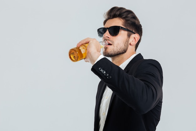Homem elegante e bonito com óculos escuros e terno preto bebendo da garrafa de cerveja na parede cinza