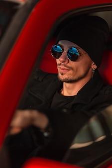 Homem elegante e bonito com óculos escuros no chapéu e casaco sentado ao volante de um carro vermelho velho