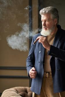 Homem elegante e brutal de meia-idade com barba olhando para longe enquanto fuma um charuto em pé no loft