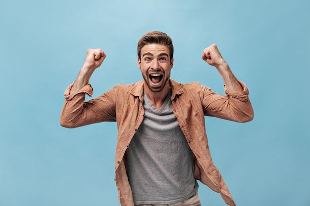 Homem elegante e positivo com penteado legal em uma camiseta cinza e uma moderna camisa marrom de manga comprida olhando para a frente e gritando