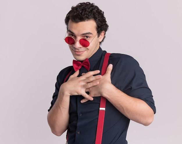 Homem elegante e satisfeito com gravata borboleta usando óculos e suspensórios, olhando para a frente com as mãos cruzadas no peito, sentindo-se grato em pé sobre uma parede branca