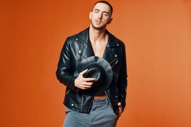 Homem elegante em jaqueta de couro preta com torso nu posando em estúdio com autoconfiança
