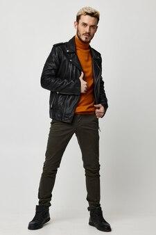 Homem elegante em jaqueta de couro, suéter amarelo e modelo de botas de calça