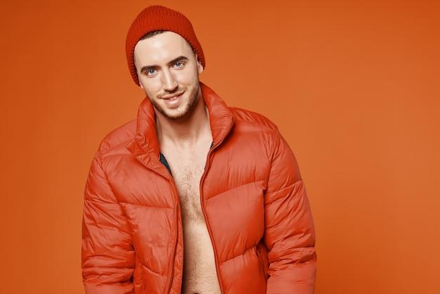 Homem elegante em jaqueta vermelha corpo nu estúdio fundo laranja