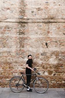 Homem elegante em pé com o ciclo na frente da parede de tijolo velho