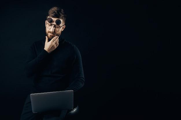 Homem elegante em roupas pretas e óculos flip-up de brainstorming na idéia sentado com o laptop.