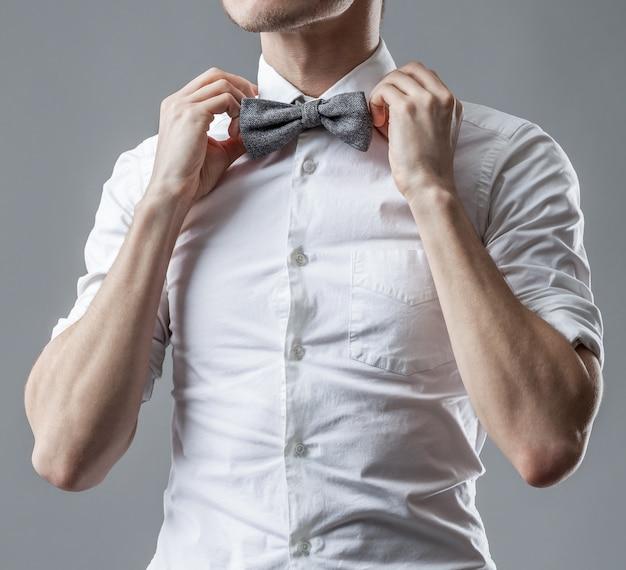 Homem elegante em uma camisa branca clássica, corrigindo sua gravata borboleta. o estilo oficial de roupas.