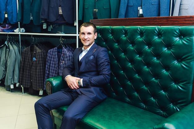 Homem elegante fica trajes de loja em um sofá de couro verde