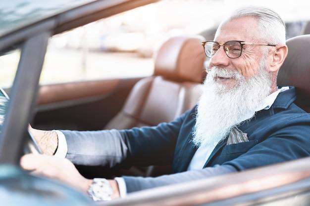 Homem elegante hipster dirigindo carro conversível - empresário sênior se divertindo com cabriolet auto - moda, conceito elegante e de negócios - foco no rosto