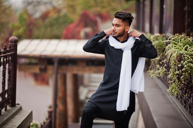 Homem elegante indiano em roupas tradicionais pretas com lenço branco posou ao ar livre.