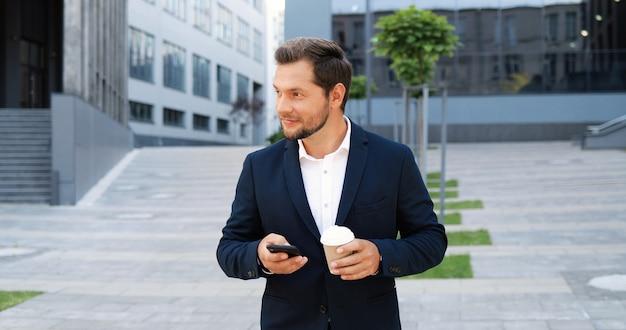 Homem elegante jovem alegre caucasiano andando na rua, tocando ou rolando no smartphone e tomando uma bebida quente pela manhã. mensagens de texto de macho feliz bonito no celular e bebendo café. ao ar livre.